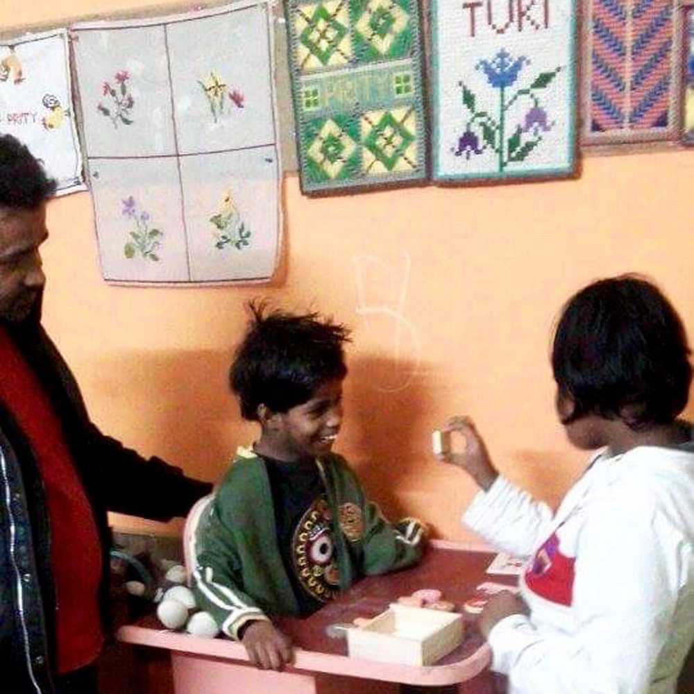 shuktara home for disabled girls - 2017 January - Pappu looks on while Muniya has a teaching moment with Guria