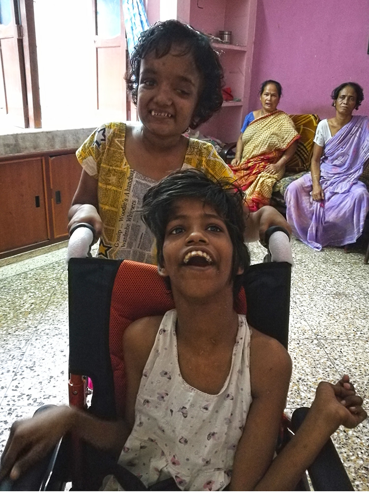 Lula Bari home for girls with disability - Moni pushing Guria in her new wheelchair