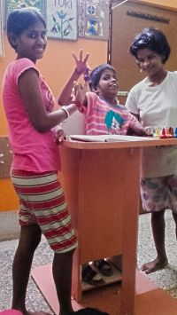 shuktara home for disabled girls - 2016 July - Guria standing in her frame with Ipshita and Lali