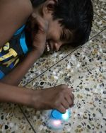 shuktara home for girls with disabilities - 2017 June - Guria lying on the floor playing with a gift from Levi