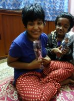 Muniya with her doll Trijntje and behind her Moni with Fenna